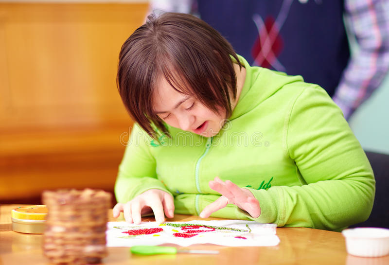 Young adult woman with disability engaged in craftsmanship in rehabilitation center. Young woman with disability engaged in craftsmanship in rehabilitation stock image