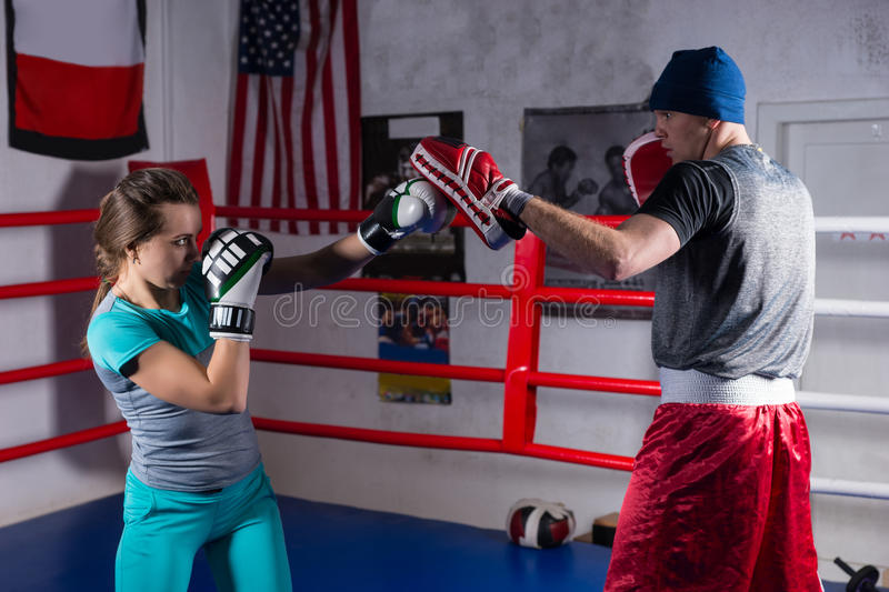 Young adult woman doing kickboxing training with her coach stock image
