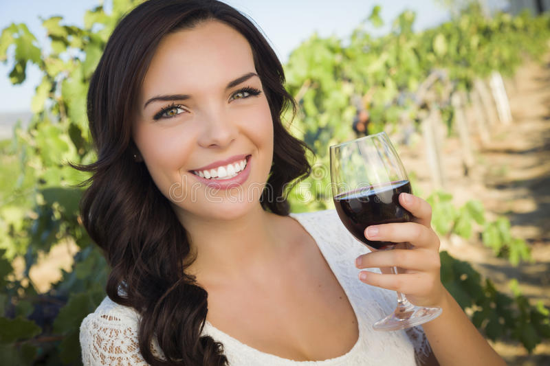 Young Adult Woman Enjoying A Glass of Wine in Vineyard. Pretty Mixed Race Young Adult Woman Enjoying A Glass of Wine in the Vineyard royalty free stock photo