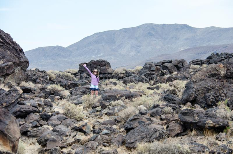 Young adult woman explores the Fossil Falls area in the Eastern Sierra Nevada Mountains of California.  stock photography