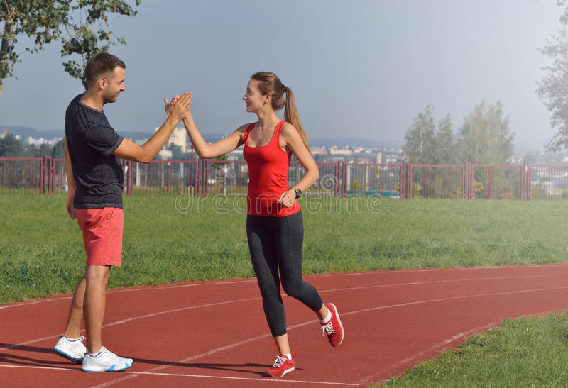 Young adult woman giving high five to partner after a run. stock photos