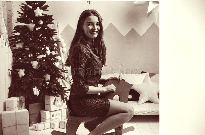 Young adult woman have fun with white toy horse on new years eve. happy new year holiday. girl sit against green christmas tree. g. Young adult woman have fun royalty free stock photos