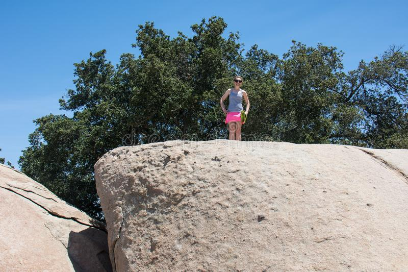 Young adult woman hiker stands on top of a giant boulder rock in San Diego California stock images