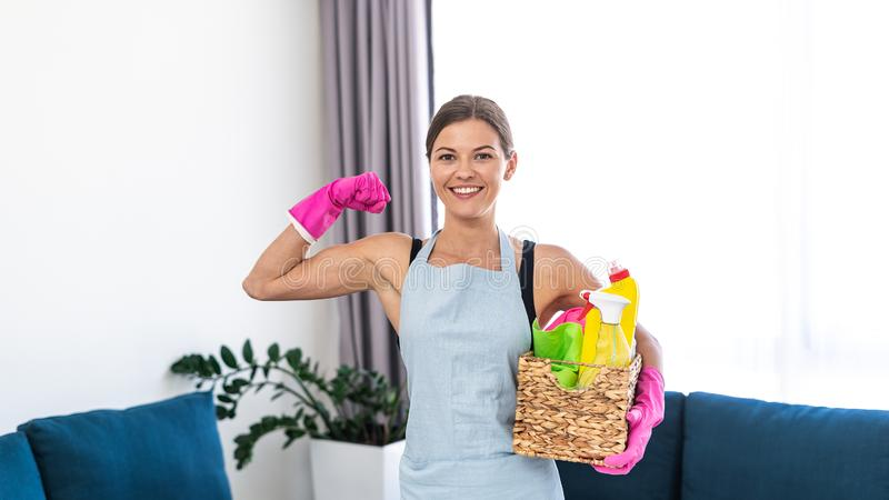 Young adult woman holding box with cleaning stuff stock photography