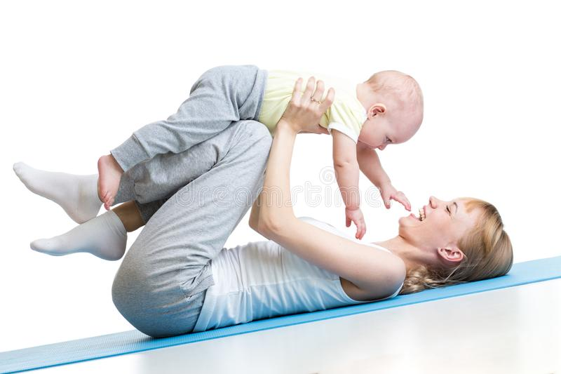 Young adult woman holding her baby son on her knees while doing yoga fitness exercises. Isolated on white background. stock photos