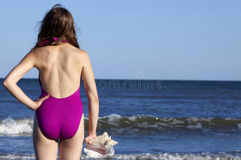 Young adult woman holding a queen conch seashell. Young adult woman in a swimsuit holding a queen conch seashell Off center for copy space stock images