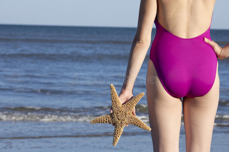 Young adult woman holding a starfish. Young adult woman in a swimsuit holding a starfish and looking at ocean Off center for copy space royalty free stock photo