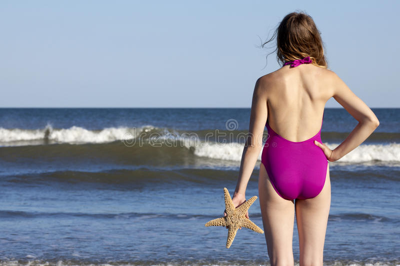 Young adult woman holding a starfish. Young adult woman in a swimsuit holding a starfish and looking at ocean Off center for copy space stock photos
