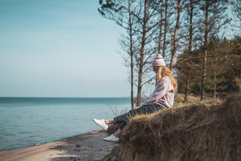 Young adult woman in pink hat sitting alone on the bluffs, looking of sea, freedom concept, peaceful atmosphere royalty free stock images