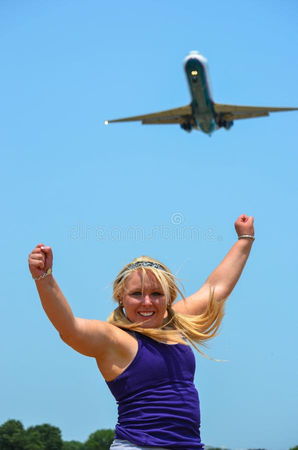 Young adult woman poses with her arms up with a large passenger jet airplane defocused in background. Concept for travel, deals. Joy, exciting, vacation stock images