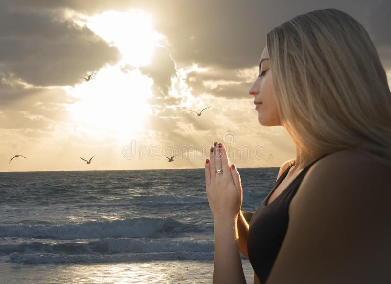 Young Adult Woman Relaxed Prayer Pose at Beach - Seagulls Orange Sunlight Sky Clouds Parting - Visual Meditation Yoga Zen -. Feelings of Empowerment Concept royalty free stock photo