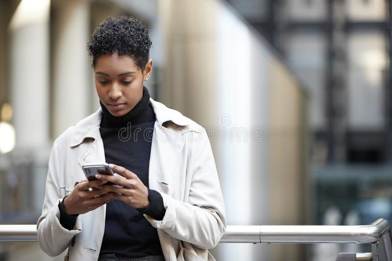 Young adult woman standing in a business area of the city using her smartphone, focus on foreground royalty free stock image