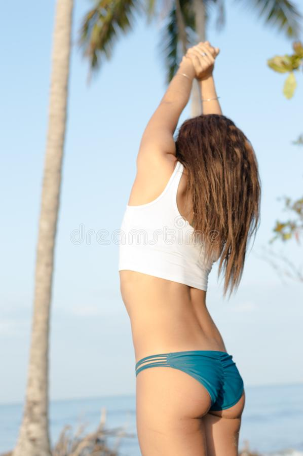 Young adult woman stretching at the beach royalty free stock images