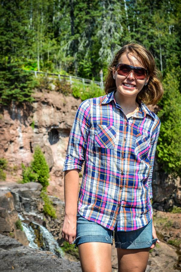 Young adult woman tourist hiker exploring Gooseberry Falls waterfall in Northern Minnesota stock photos