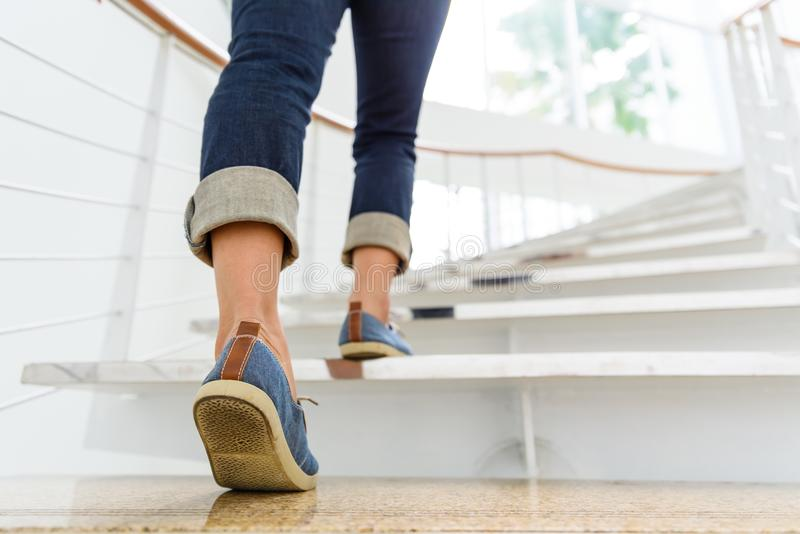 Young adult woman walking up the stairs. With sun sport background royalty free stock images