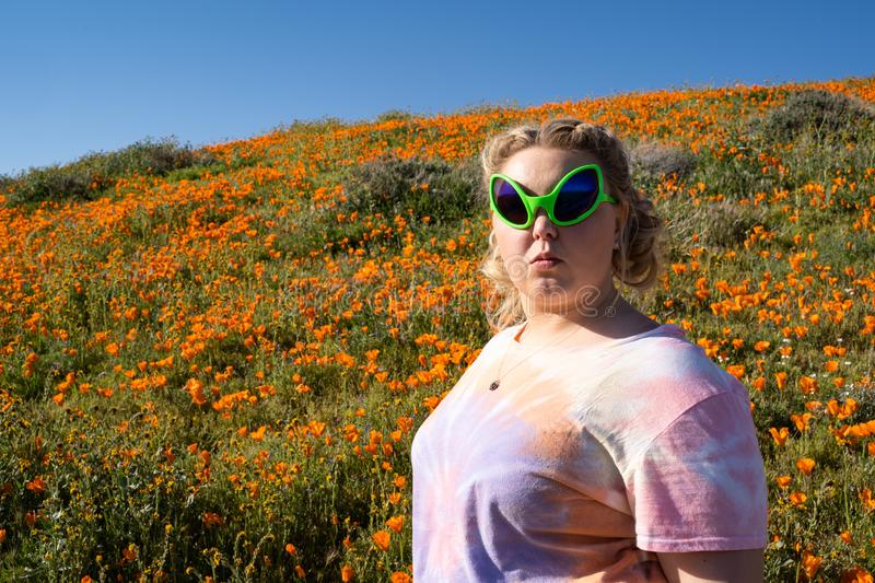 Young adult woman wearing alien sunglasses and a tie dye t-shirt stands in a field of poppies stock photo
