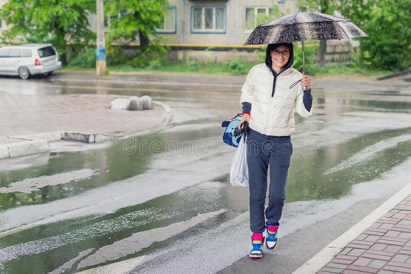 Young adult woman wearing casual sport clothes crossing road holding umbrella in hand during rain in autumn day. Girl royalty free stock photo