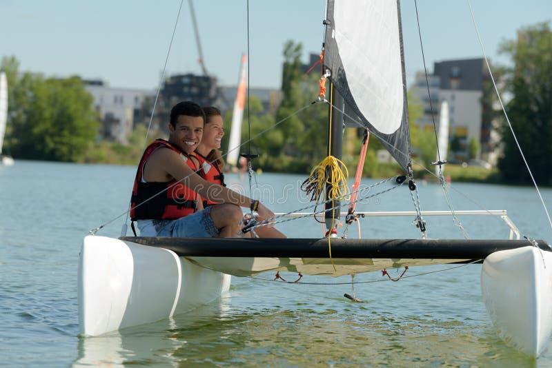 Young adults on board catamaran sailboat royalty free stock photo