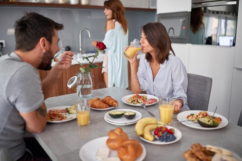 Young adults having fun while making and eating breakfast. modern, casual, lifestyle concept. Young adults having fun while making and eating breakfast. modern stock photography