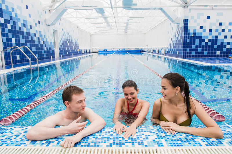 Young adults having fun talking in swimming pool indoors stock images