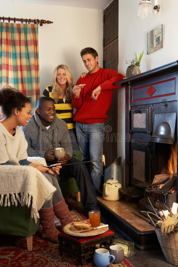 Young adults making toast on open fire. Having fun looking off camera stock photos