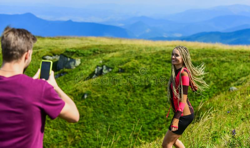 Young adventurers. Couple taking photo. Couple in love hiking mountains. Lets take photo. Capturing beauty. Man and. Women posing mobile photo. Summer vacation royalty free stock image