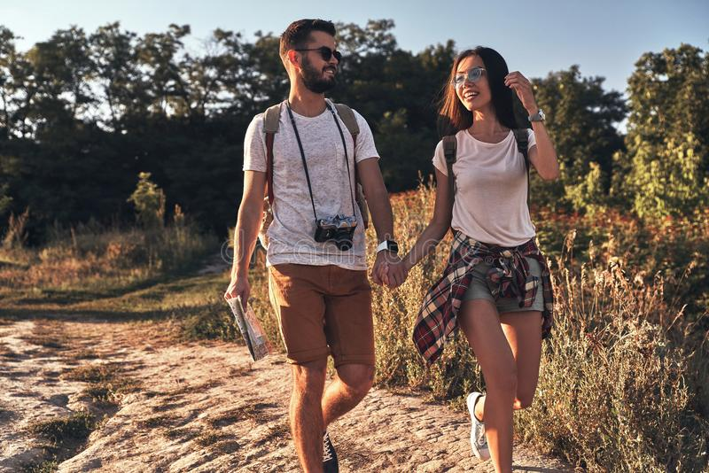 Young adventurers. Beautiful young couple holding hands and smiling while walking outdoors royalty free stock photo