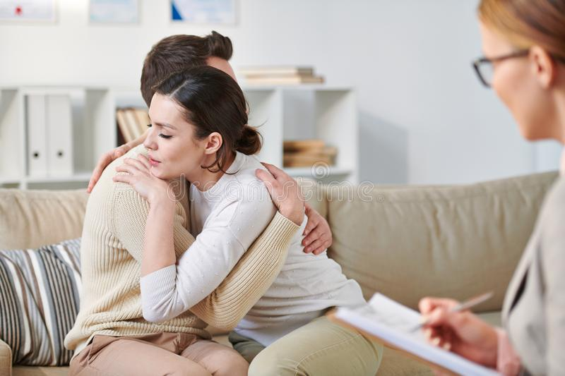 Reconciliation. Young affectionate couple sitting on couch in embrace after reconciliation in front of their counselor royalty free stock image
