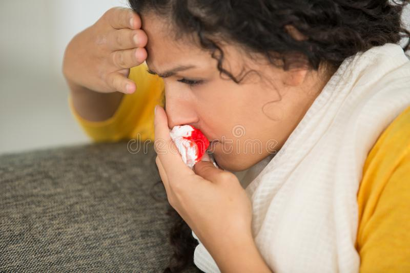 Young afraid woman with bloody nose. Young afraid woman with a bloody nose royalty free stock photography