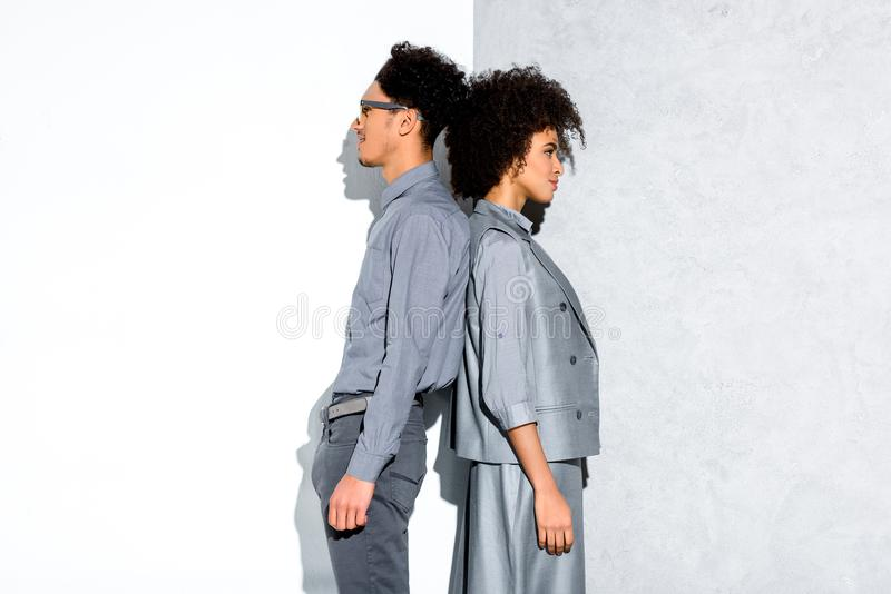Young african amercian smiling couple in grey suits standing back to back on grey and white stock photos