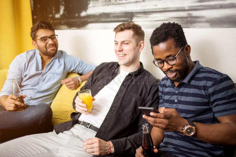 Male friends watching sports on tv at home stock photo