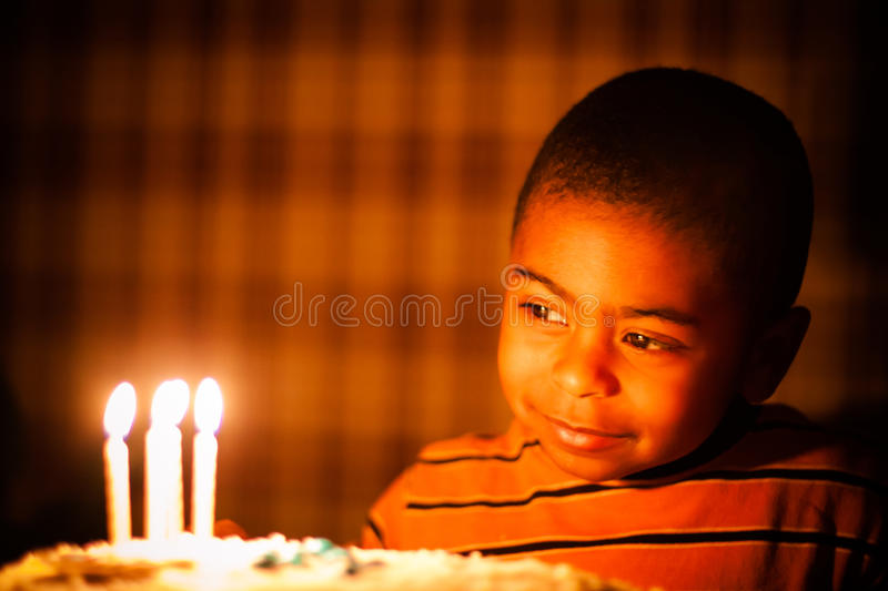 Young african american boy looking at birthday candles. Thoughtfully stock photo