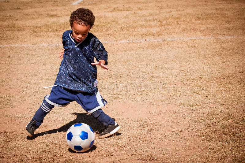 Young African American boy playing soccer royalty free stock photo
