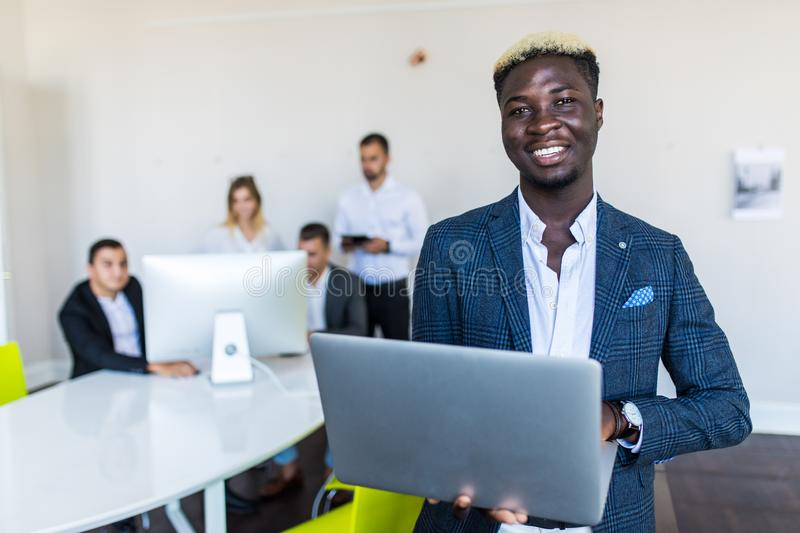 Young African-American Business leader standing in front of business team smiling stock photos