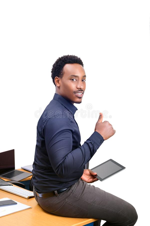 Young African American business man sitting on top of his desk in office royalty free stock image