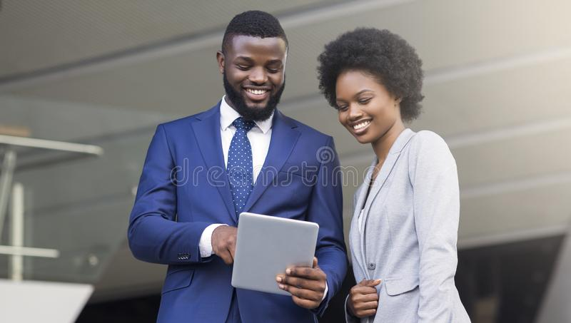 Young african american business partners using digital tablet outdoors royalty free stock photography