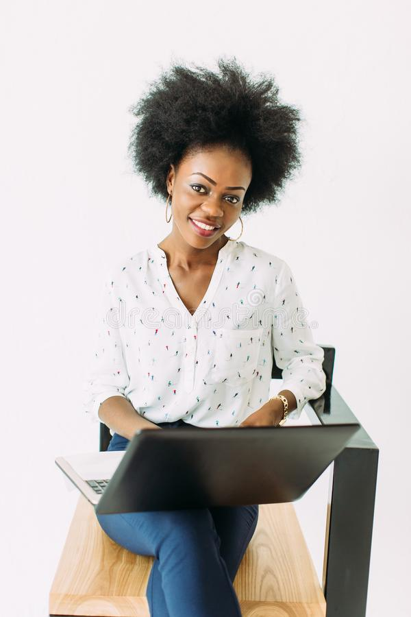 Young african american business woman typing on laptop while sitting on the chair, isolated on white royalty free stock photo