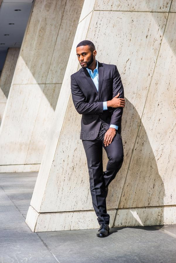 Young African American Businessman with beard in New York City. Wearing black suit, leather shoes, bending leg, crossing arm, standing by column on street royalty free stock photos