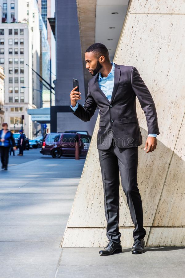 Young African American Businessman with beard self recording speech on cell phone outside office building in New York City stock photo