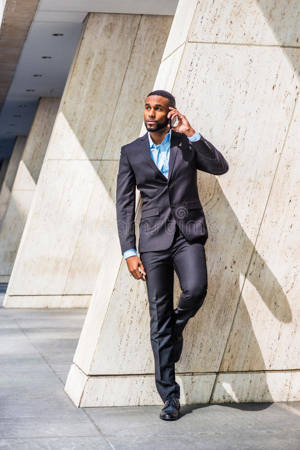 Young African American Businessman with beard talking on cell phone outside office in New York. City, wearing black suit, leather shoes, standing by column on royalty free stock images