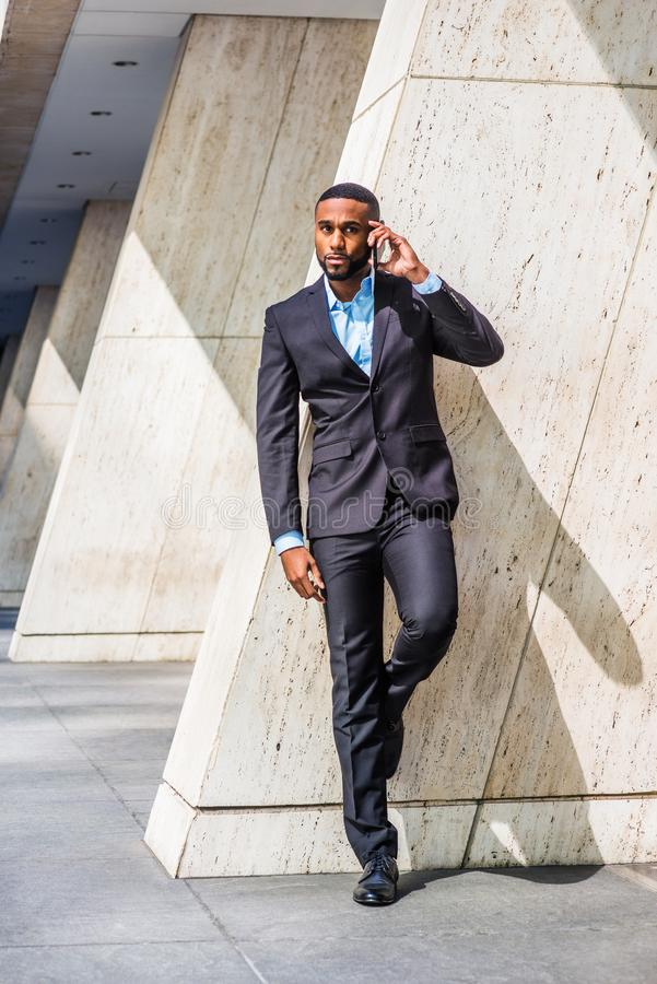 Young African American Businessman with beard talking on cell phone outside office in New York. City, wearing black suit, leather shoes, standing by column on stock image