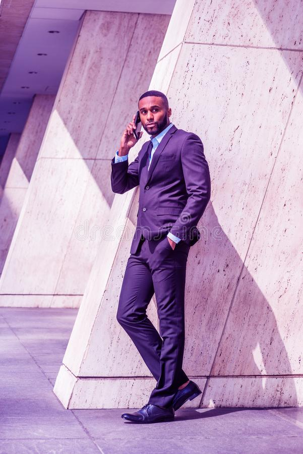 Young African American Businessman with beard talking on cell phone outside office in New York. City, wearing black suit, leather shoes, standing by column on royalty free stock photo