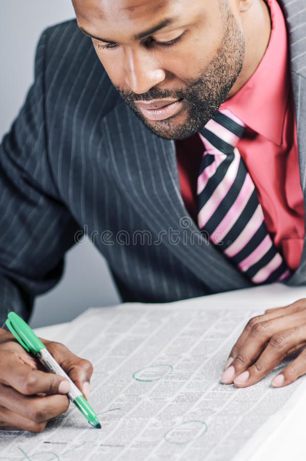 Young African American Businessman Being Sneaky On Laptop. Studio shot of a young African American Businessman using a laptop computer stock images