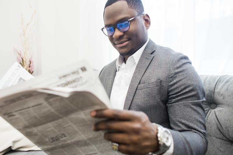 Young African American businessman in a gray suit reading a newspaper while sitting on a sofa. stock photography