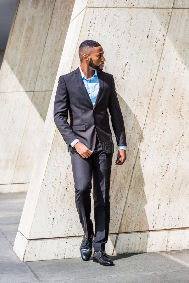 Young African American Businessman relaxing outside in New York. Young African American Businessman with beard, wearing black suit, leather shoes, standing by stock photography