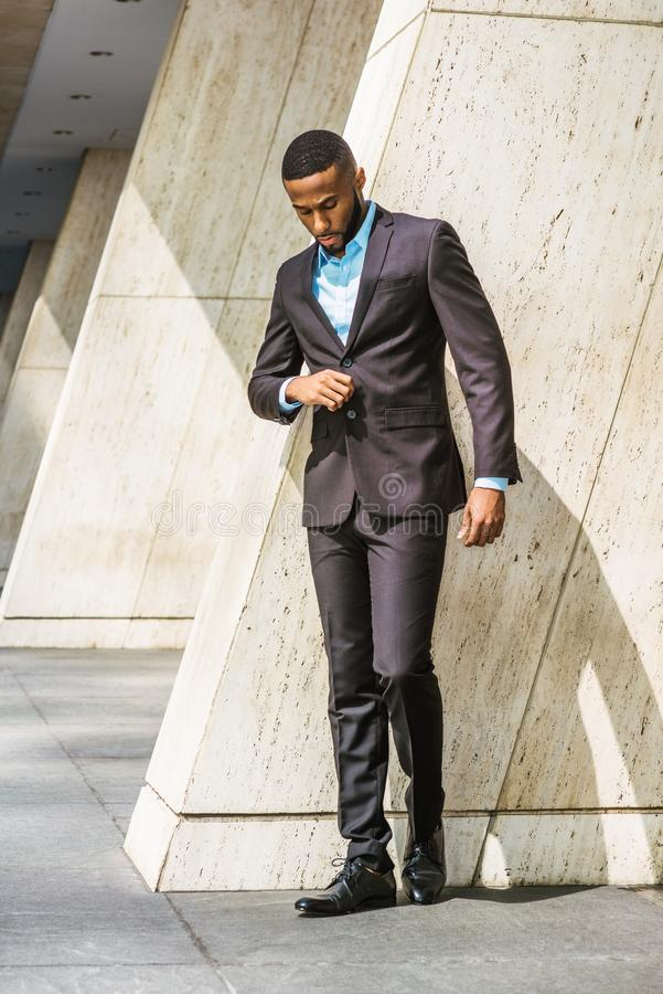 Young African American Businessman thinking outside in New York. Young African American Businessman with beard, wearing black suit, leather shoes, standing by stock photos