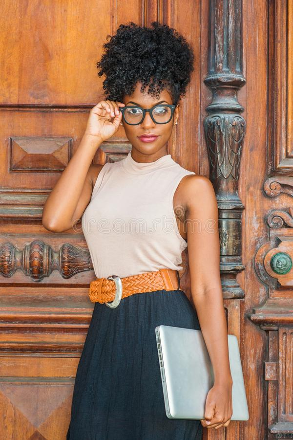 Young African American College Student with afro hairstyle, eye glasses, wearing sleeveless light color top, black skirt, belt, stock images