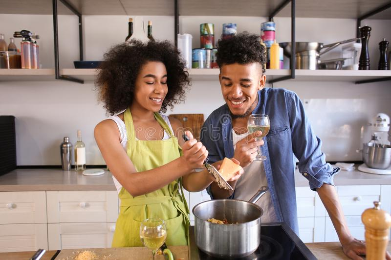 Young African-American couple cooking together in kitchen royalty free stock image