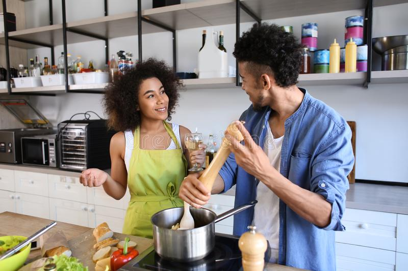 Young African-American couple cooking together in kitchen stock images