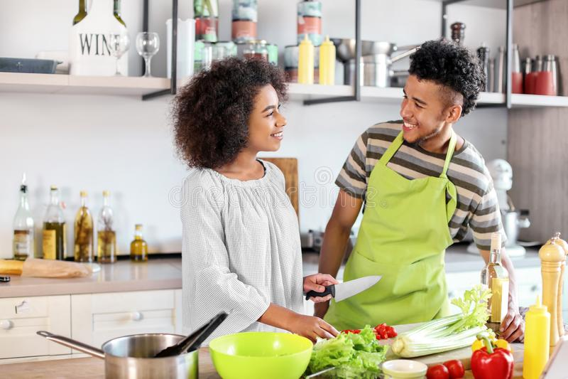 Young African-American couple cooking together in kitchen royalty free stock images